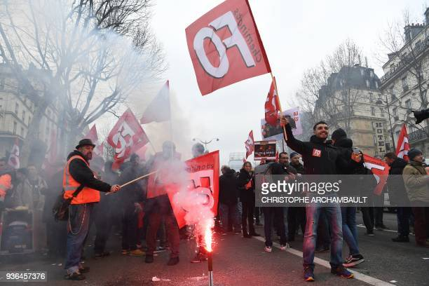 French railways workers hold banners and flares as they take part in a demonstration to protest against French government's string of reforms on...