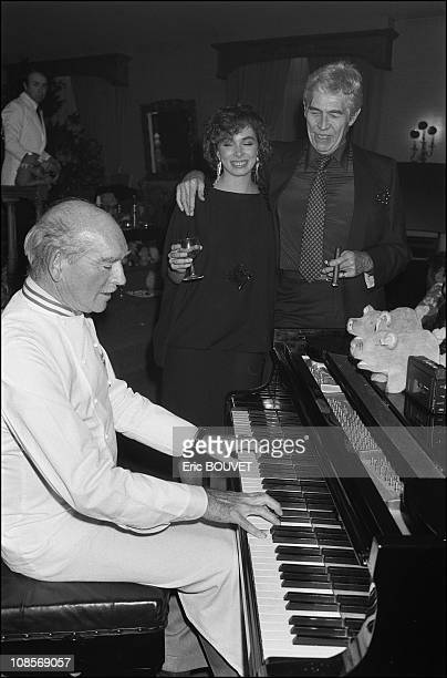 French record producer Eddie Barclay plays the piano during a party in France on April 05th 1984 James Coburn and his girlfriend Lisa Alexander are...