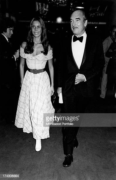 French recordcompany owner Eddie Barclay walking with his young wife at Olympia Paris 1970s