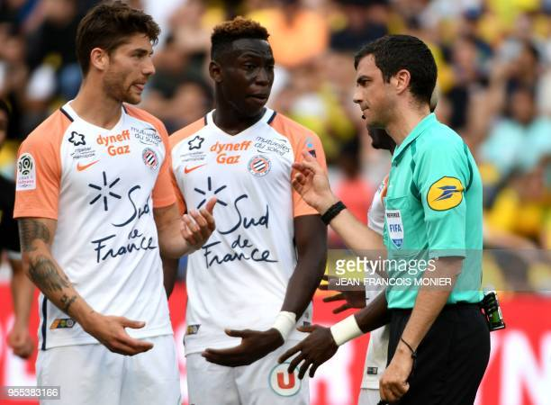 French refere Franck Schneider talks to Montpellier's French midfielder Paul Lasne and Montpellier's French midfielder Junior Sambia during the...