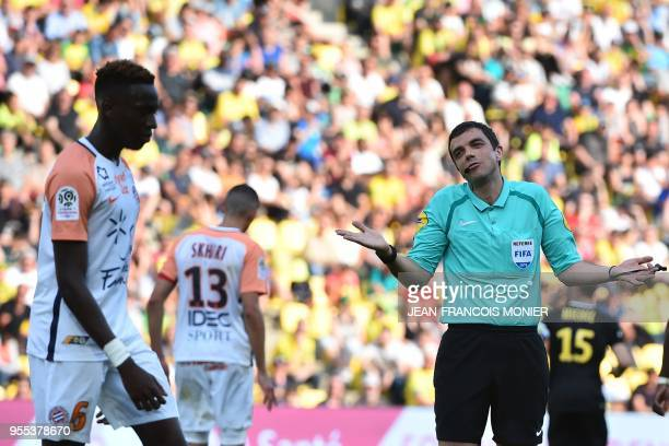 French refere Frank Schneider reacts and gestures towards Montpellier's French midfielder Junior Sambia during the French L1 football match between...