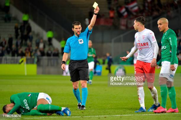 French refere Jeremy Stinat shows a yellow card to Nimes' French defender Florian Miguel after he fouled Saint-Etienne's French forward Arnaud Nordin...