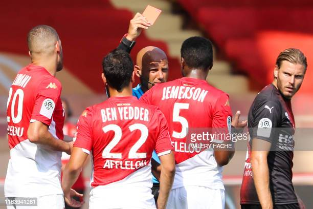 French referee Amaury Delerue gives a red card to Monaco's Brazilian defender Jemerson during the French L1 football match between Monaco and Nimes...