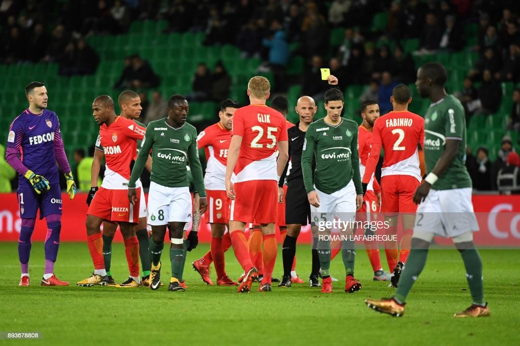 French referee Amaury Delerue (C) gives a yellow card to Saint-Etienne's French midfielder Vincent Pajot (4thR) during the French L1 football match between Saint-Etienne (ASSE) and Monaco (ASM) on December 15, 2017, at the Geoffroy Guichard stadium in Saint-Etienne, central-eastern France. /