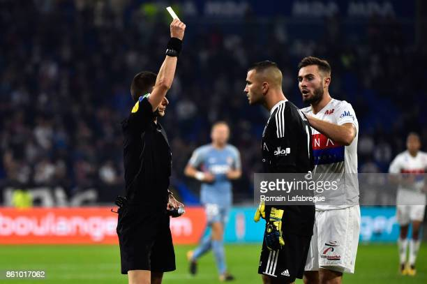 French referee Bastien Benoit gives a yellow card to Anthony Lopes of Lyon during the Ligue 1 match between Olympique Lyonnais and AS Monaco at Stade...