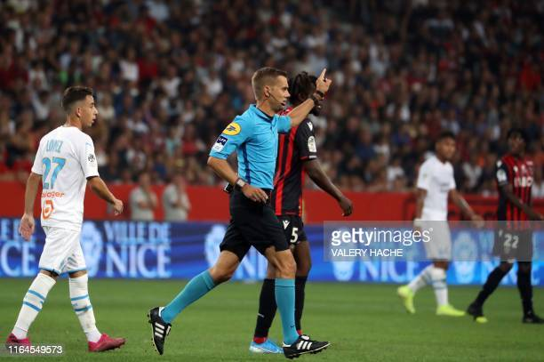 French referee Clement Turpin gestures as he haltes the game after supporters shouted homophobic songs and brandished banners during the French L1...