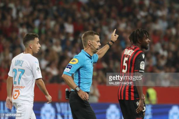 TOPSHOT French referee Clement Turpin gestures as he haltes the game after supporters shouted homophobic songs and brandished banners during the...