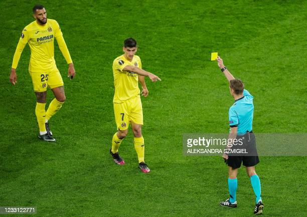 French referee Clement Turpin presents a yellow card to Villarreal's French midfielder Etienne Capoue during the UEFA Europa League final football...