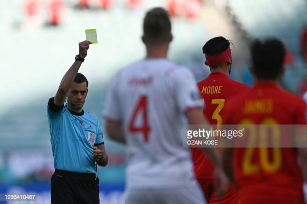 French referee Clement Turpin presents a yellow card to Wales' midfielder Kieffer Moore after a foul during the UEFA EURO 2020 Group A football match...