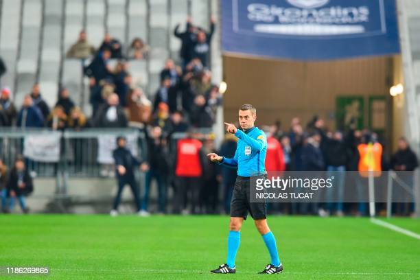 French referee Clement Turpin stops the game as fans stand on the pitch during the French L1 football match between FC Girondins de Bordeaux and...