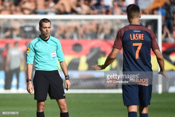 French referee Clement Turpin talks to Montpellier's French midfielder Paul Lasne during the French Ligue 1 football match between Paris SaintGermain...