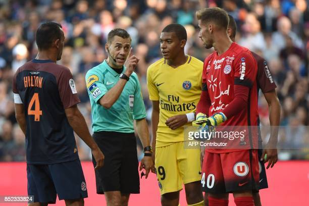 French referee Clement Turpin warns Montpellier's French goalkeeper Benjamin Lecomte as Montpellier's Brazilian defender Vitorino Hilton and Paris...