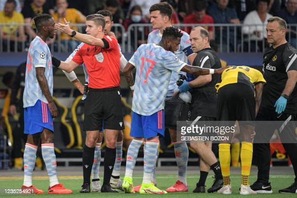 French referee Francois Letexier asks Manchester United's English defender Aaron Wan-Bissaka to leave the pitch after showing him a red card for a...