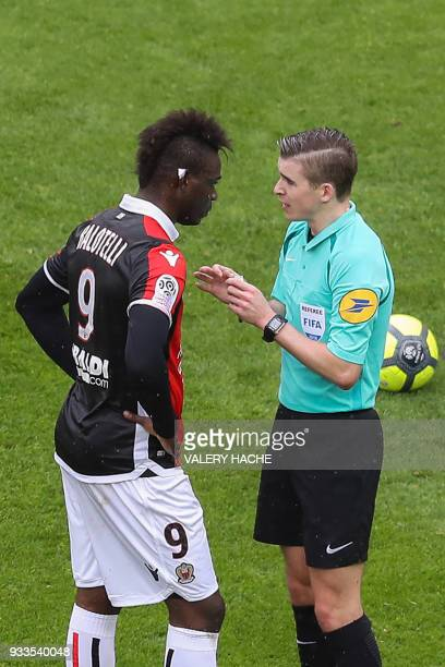 French referee Francois Letexier talks to Nice's Italian forward Mario Balotelli during the French L1 football match Nice vs Paris SaintGermain on...