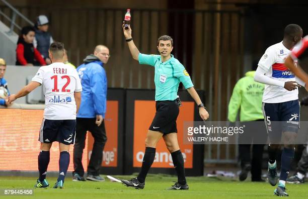 French referee Frank Schneider holds a bottle which was thrown onto the pitch during the French L1 football match Nice vs Lyon at The 'Allianz...