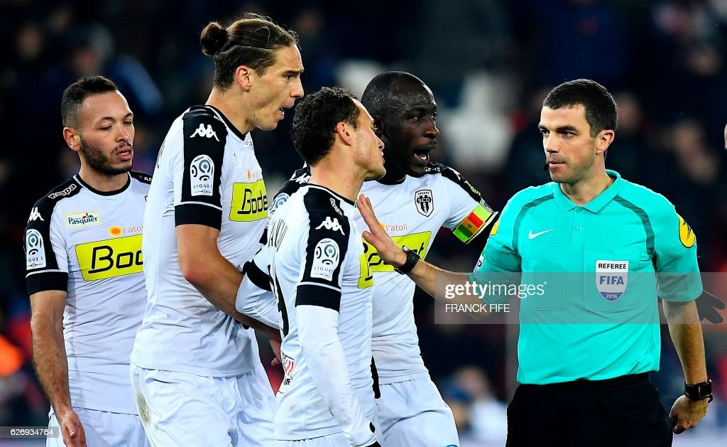 French referee Frank Schneider (R) speaks to Angers' players during the French L1 football match between Paris Saint-Germain (PSG) and Angers at the Parc des Princes stadium in Paris on November 30, 2016. /