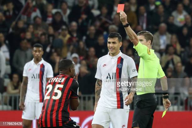 French referee François Letexier shows a red card to Nice's French midfielder Wylan Cyprien next to Paris Saint-Germain's Argentine midfielder...