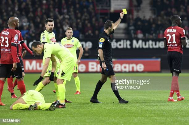 French referee Jerome Brisard gives a yellow card to Guingamp's French midfielder Marcus Thuram during the French L1 football match Guingamp vs...