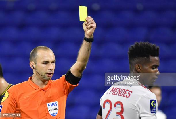 French referee Jerome Brisard shows a yellow card to Lyon's Brazilian defender Thiago Mendes during the French L1 football match between Olympique...