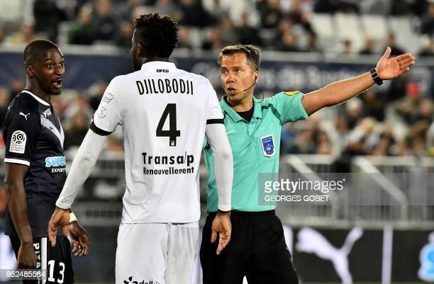 French referee Johan Hamel asks arguing players Bordeaux' Senegalese midfielder Younousse Sankhare and Dijon's Senegalese defender Papy Djilobodji go...