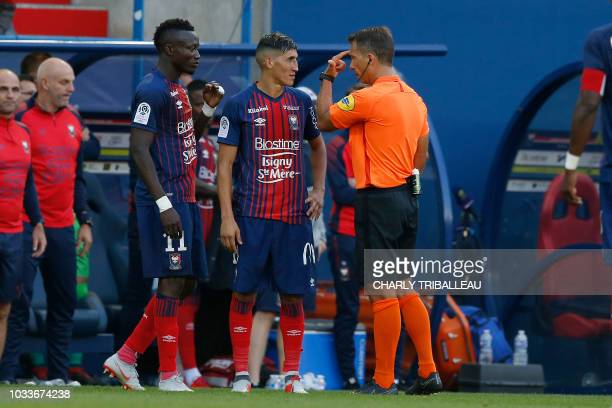 French referee Johan Hamel explains to Caen's Moroccan midfielder Faycal Fajr the incident between Caen's FrenchGuinean midfielder Baissama Sankoh...