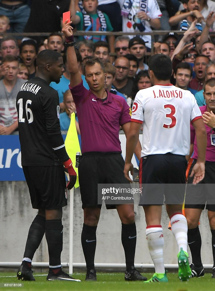 French referee Johan Hamel (C) gives a red card to Lille's French goalkeeper Mike Maignan (L) as Lille's Paraguay defender Junior Alonso (R) looks on during the French Ligue 1 football match between Strasbourg (RCSA) and Lille (LOSC) at The Meinau Stadium in Strasbourg, eastern France on August 13, 2017. /