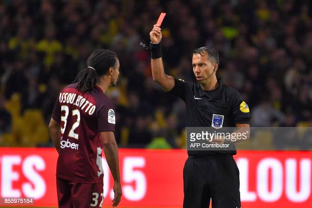 French referee Johan Hamel gives a red card to Metz' French defender Benoit AssouEkotto during the French L1 football match Nantes vs Metz at the La...