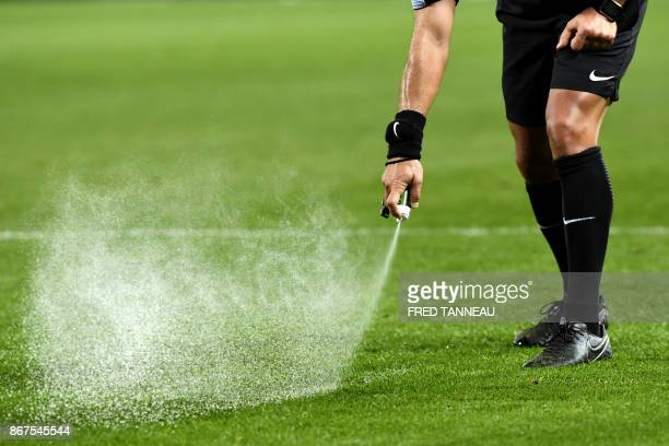French referee Johan Hamel sprays the position of a free kick during the French L1 football match Guingamp against Amiens October 28, 2017 at the...