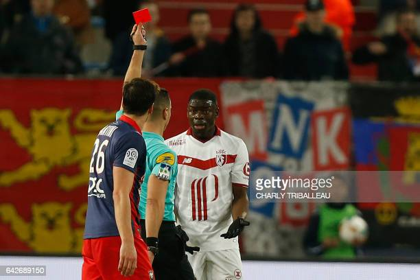 French referee Karim Abded gives a red card to Lille's French defender Adama Soumaoro during the French L1 football match between Caen and Lille on...