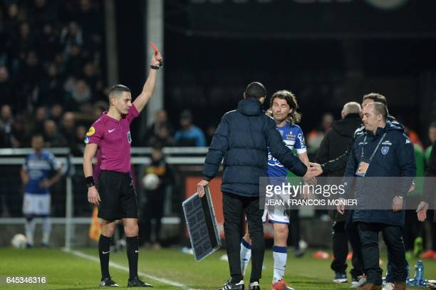 French referee Karim Abed gives a red card to Bastia's French midfielder Yannick Cahuzac during the French L1 football match between Angers and...