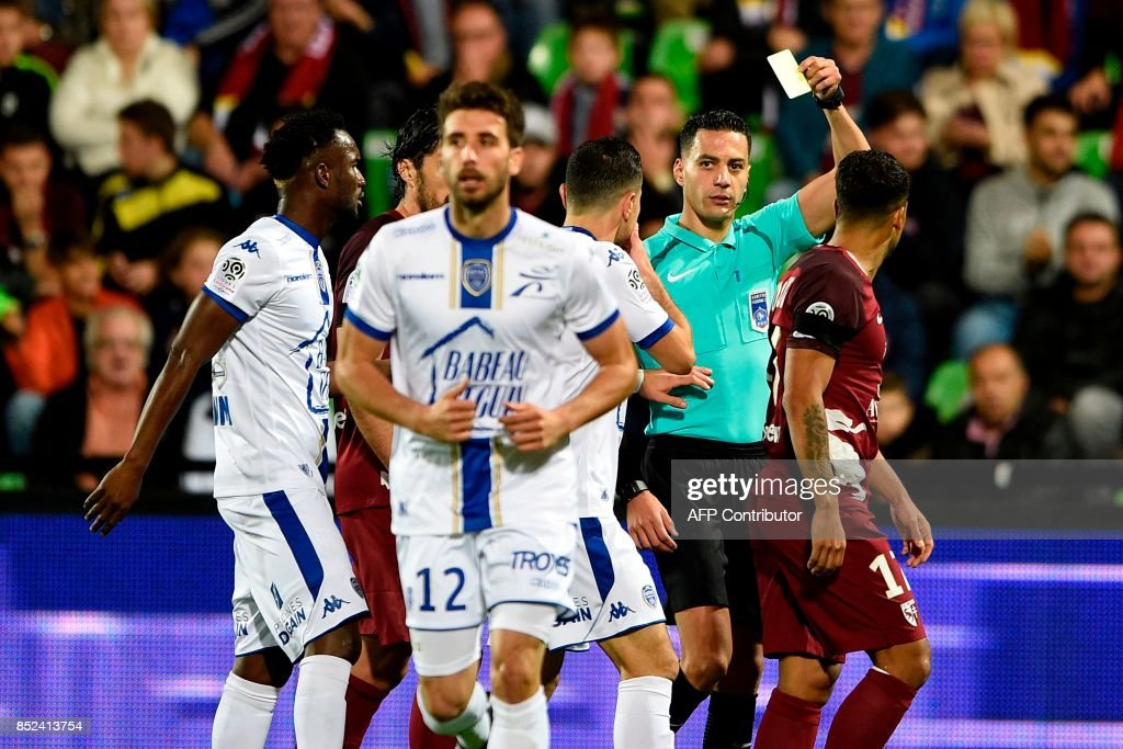 French referee Karim Abed (Rear R) gives a yellow card to Troyes' French defender Mathieu Deplagne (Front C) during the French L1 football match between Metz (FCM) and Troyes (ESTAC) on September 23, 2017 at the Saint-Symphorien stadium in Longeville-Les-Metz, eastern France. VERHAEGEN