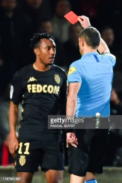 French referee Mikael Lesage gives a red card to Monaco's Portuguese midfielder Gelson Martins during the French L1 football match between Nimes and...