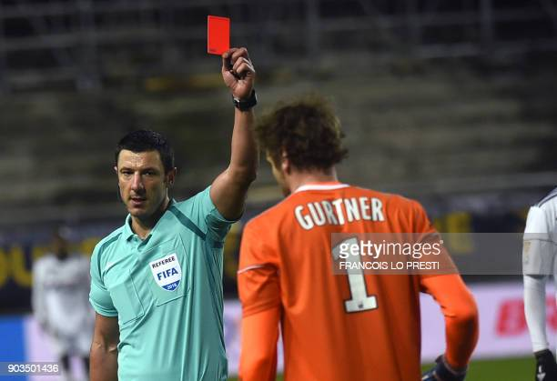 French referee Nicolas Rainville gives a red card to Amiens's goalkeeper Regis Gurtner during the French League Cup quarterfinal football match...