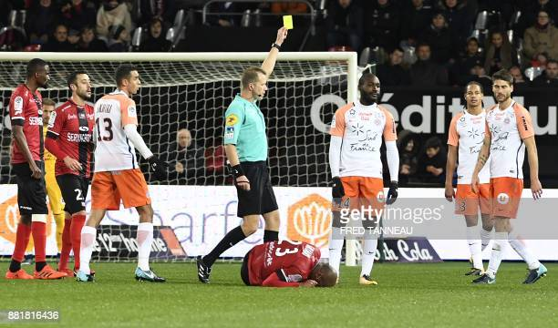 French referee Olivier Thual gives a yellow card to Montpellier's French forward Giovanni Sio during the French L1 footbal match between Guingamp and...
