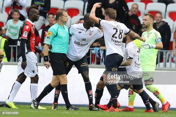 French referee Olivier Thual looks at players arguing during the French L1 football match Nice vs Dijon on November 5 2017 at the 'Allianz Riviera'...