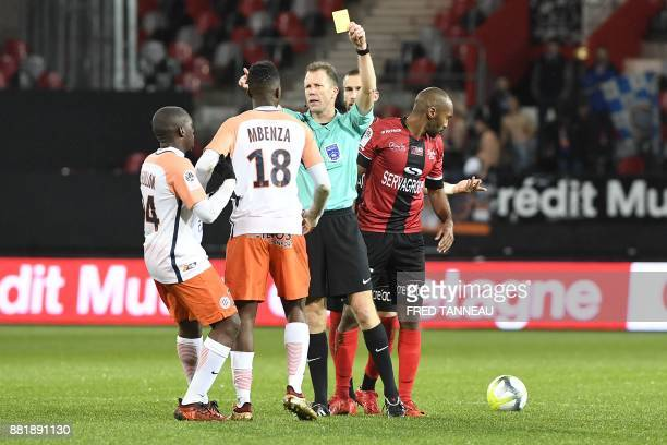 French referee Olivier Thual shows a yellow card to Montpellier's Belgian forward Isaac Mbenza during the French L1 match Guingamp against...