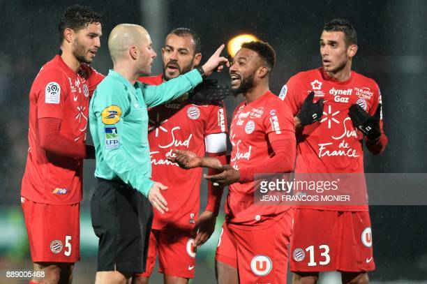 French referee Stephane Jochem gestures as he speaks with Montpellier's French midfielder Stephane Sessegnon and others during the French L1 Football...