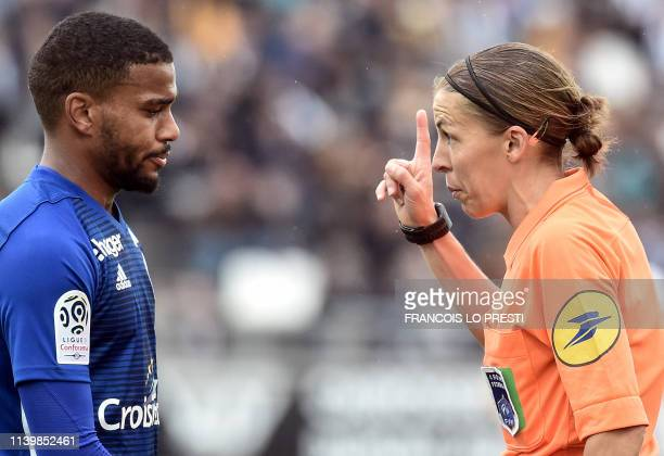 French referee Stephanie Frappart gestures next to Strasbourg's French midfielder Samuel Grandsir during the French L1 football match between Amiens...