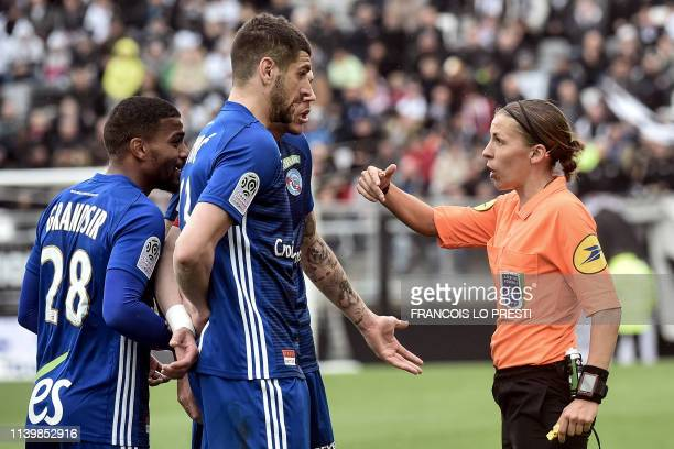 French referee Stephanie Frappart gestures next to Strasbourg's French midfielder Samuel Grandsir and Strasbourg's Serbian defender Stefan Mitrovic...