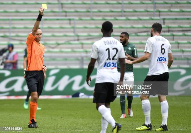 French referee Thomas Leonard gives a yellow card to Amiens' French midfielder Thomas Monconduit during the French L1 football match between AS...