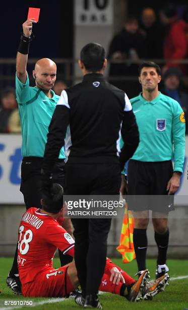 French referee Tony Chapron gives a red card to Rennes' French midfielder Morgan Amalfitano during the French L1 football match between Strasbourg...