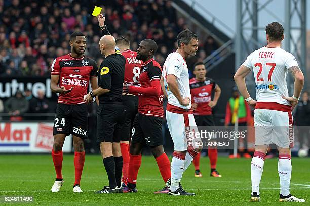 French referee Tony Chapron shows a yellow card to Guingamp's French defender Marcus Coco during the French L1 football match between Guingamp and...