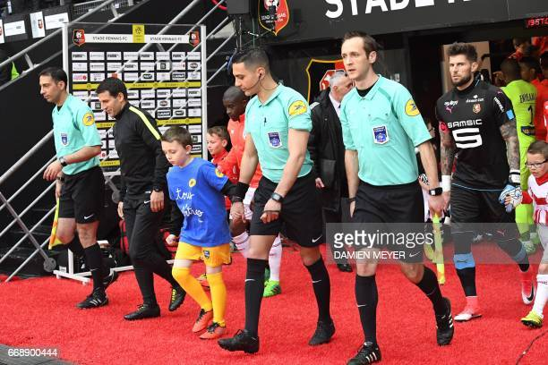French referees Huseyin Ocak Jeremy Stinat Karim Abed and Benjamin Pages enter the pitch prior to the French L1 football match Rennes against Lille...