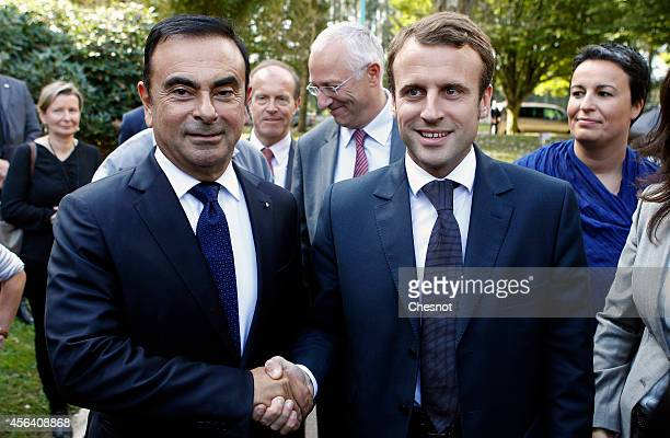 French Renault car maker CEO Carlos Ghosn shakes hands with French Economy Minister Emmanuel Macron on September 30 2014 in Sandouville France Car...