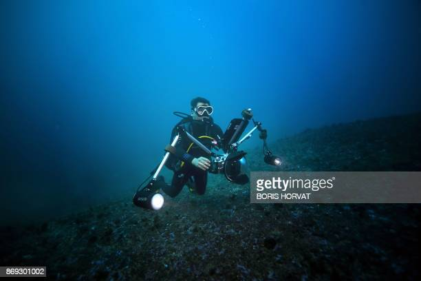 French reporter Alexis Rosenfeld tests a camera connected to a geotracking tablet during a diving off the coast of Marseille on November 1 2017...
