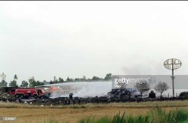 French rescue workers attempt to put out the flames of the wreckage of an Air France Concorde jet July 25 2000 that crashed shortly after take off in...