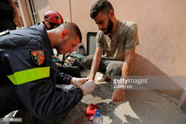 French rescuer treats a Lebanese volunteer in Beirut's Gemayzeh neighbourhood, wounded while clearing debris from buildings damaged by a blast in the...