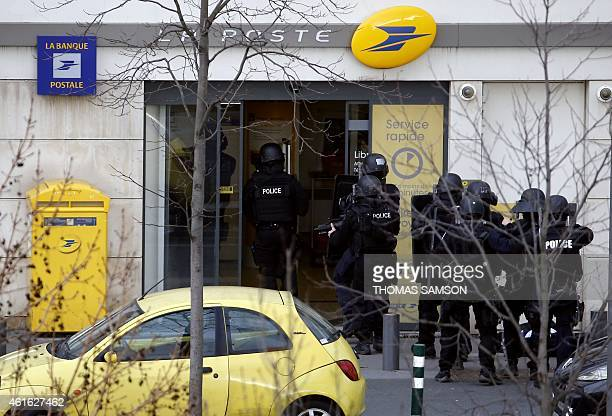 French Research and Intervention Brigades police officers enter a post office after an armed man who was holed up with two hostages has surrender on...