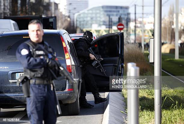French Research and Intervention Brigades policemen officers stand guard near the post office where an armed man is holed up with two hostages on...
