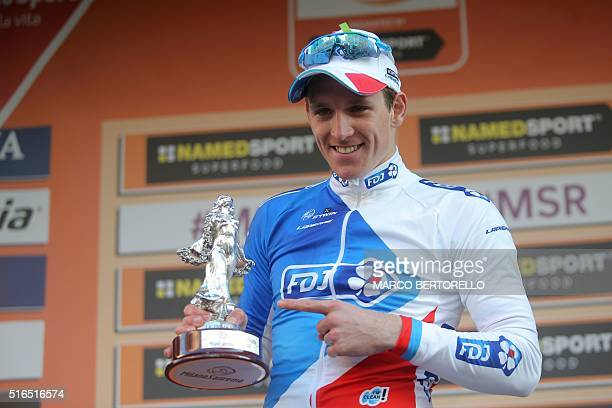 French rider Arnaud Demare poses with the trophy on the podium of the 107th edition of the Milan San Remo cycling race on March 19 2016 in San Remo...
